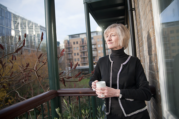 A woman stood on a balcony holding a coffee mug