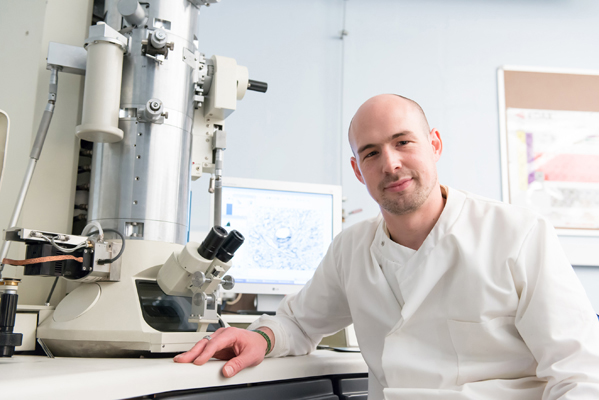 A research scientist next to a large microscope