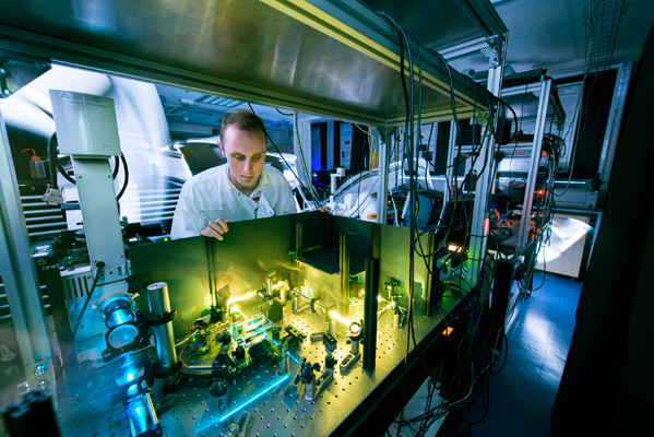 A researcher inspecting laser equipment in a laboratory