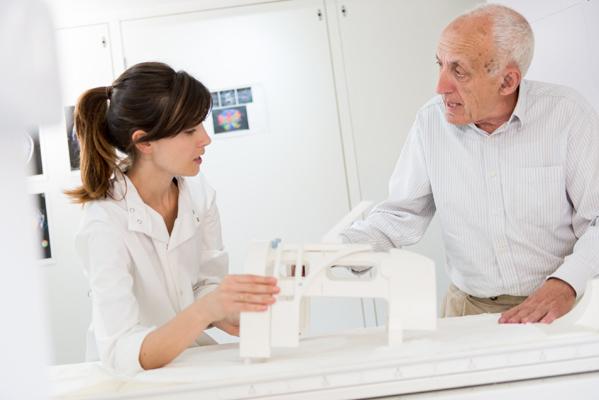 A doctor demonstrating an MRI scanner to an elderly man
