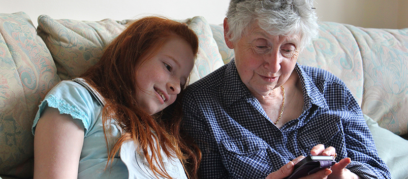 kids-girl-showing-grandmother-mobile-phone