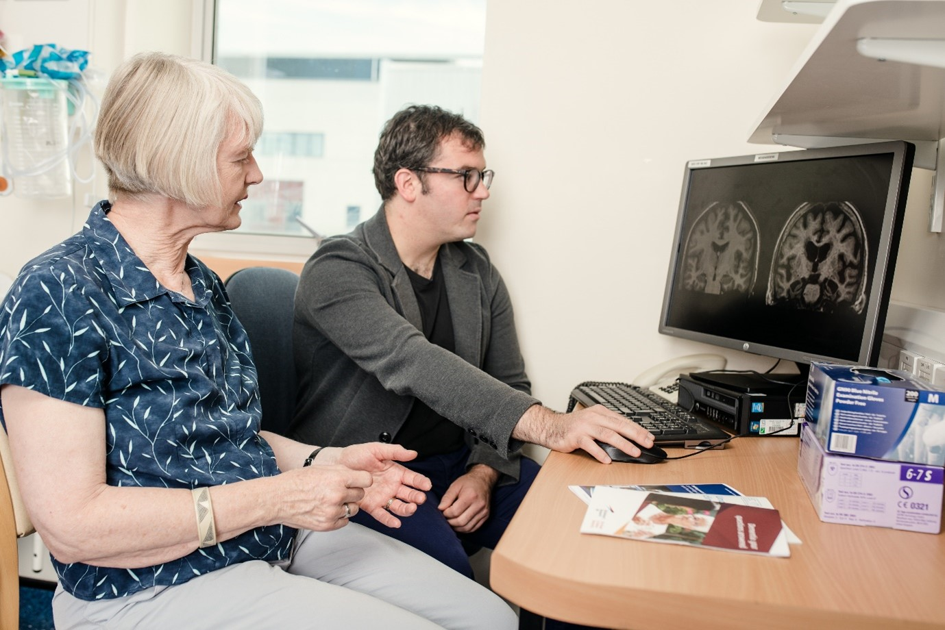 older woman looking at brain scans on pc monitor