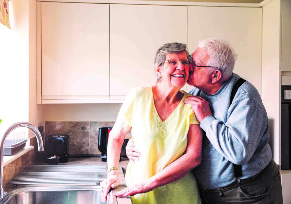 Elderly man holds his wife as he kisses her on the cheek as she stands at the kitchen sink