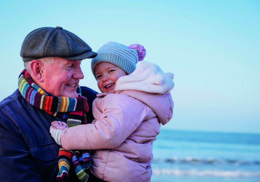 Senior man on the coast. Its cold outside so they are wrapped up warm. The man is carrying a little girl in his arms