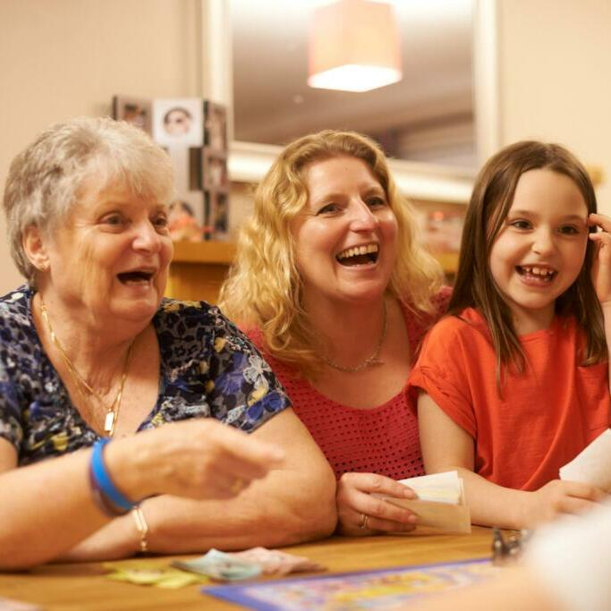 Three family members playing a board game
