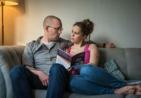 couple reading guide on sofa
